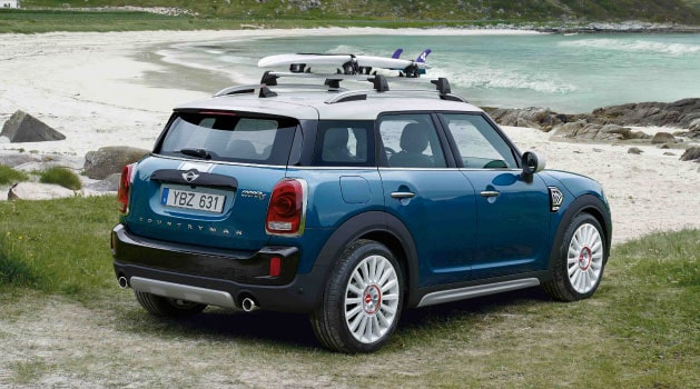 Rear view of the MINI Countryman in blue parked on the beach.