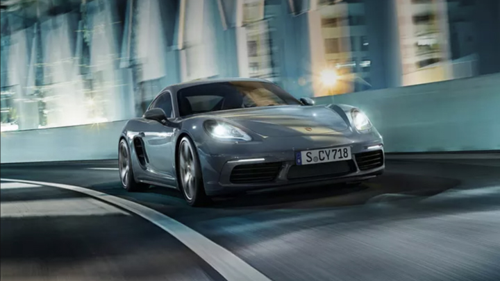 Porsche 718 driving on the road.