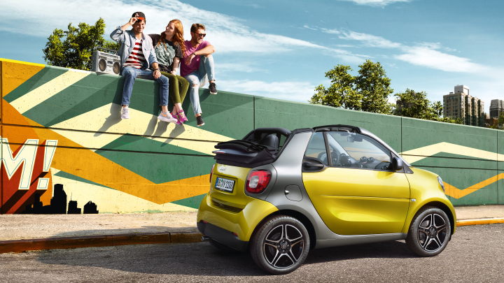 Yellow smart ForTwo Cabrio parked on the road.
