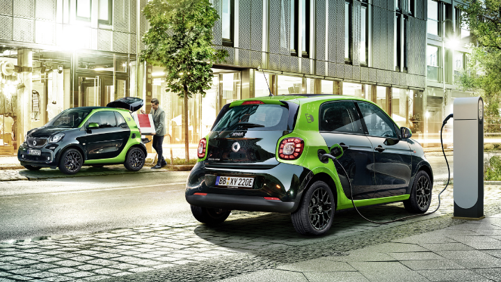 Black and green smart Electric Drive on the road.