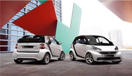 Two white approved used smart cars parked.