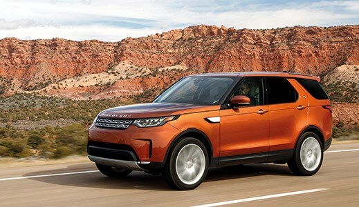 Orange Land Rover Discovery in the mountains.