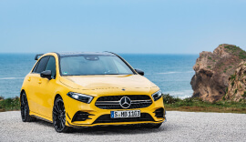 Front view of the yellow Mercedes-Benz AMG A35 parked by the sea.