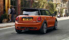 Back view of the orange MINI Hatch on the road.