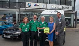 Stratstone staff stood with the Defibrillators team outside the showroom.
