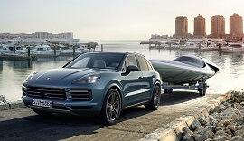 Blue 3rd Generation Porsche Cayenne towing a boat.
