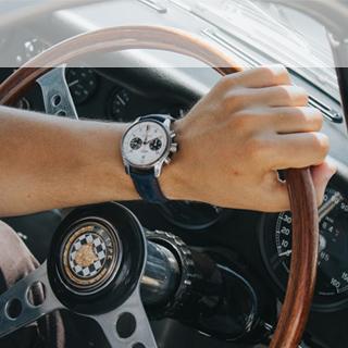 Hand on steering wheel of Jaguar Lightweight E-Type.